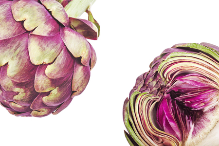 Purple artichokes, one of them cut in half, on a white background. Top view Stock Photo