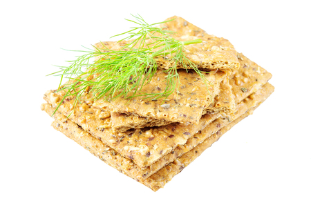 Stack of crispy wheat flatbread crackers with sprig of dill isolated on a white background  Stock Photo