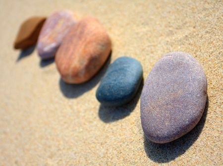 Colored pebbles on the yellow sand Stock Photo