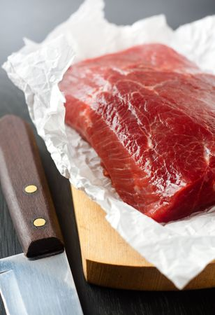 Large piece of uncooked beef lying on the white paper and a knife photo