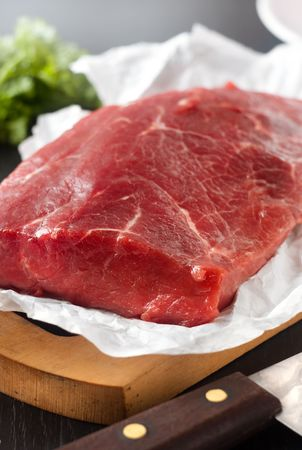Large piece of uncooked beef lying on the white paper and a knife