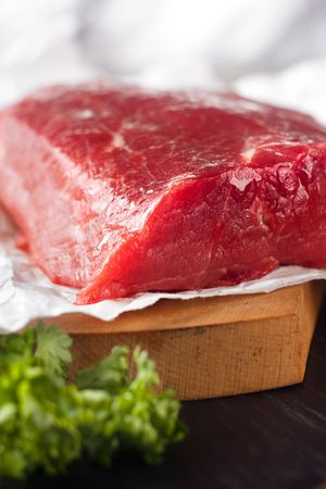 Large piece of uncooked beef lying on the white paper photo