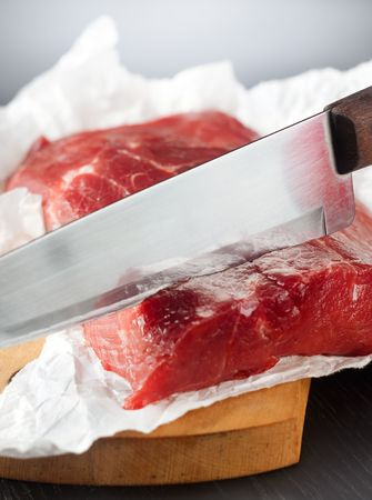 Knife cutting a large piece of uncooked beef  Stock Photo