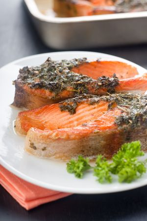 Closeup of baked trout with herbs on the white ceramic plate photo
