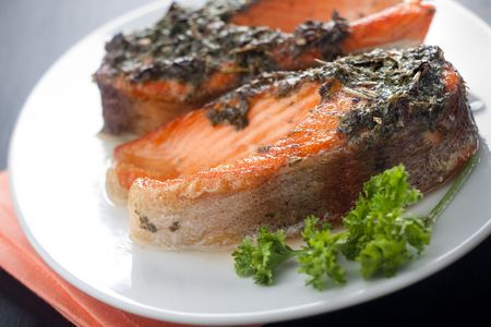Closeup of baked trout with herbs on the white ceramic plate
