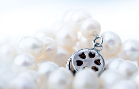 Closeup of natural freshwater pearl necklace and a metal clasp, shallow focus