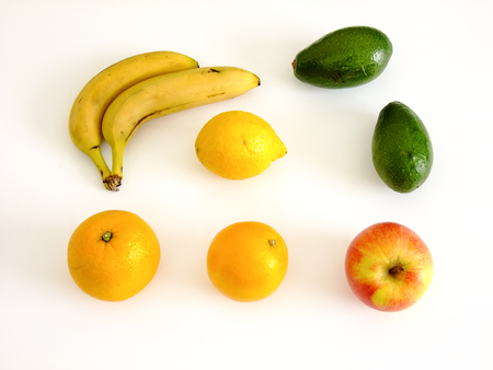 Flat Lay Composition of Bananas, Oranges, Apples, Lemon and Avocado in white Background Stock Photo