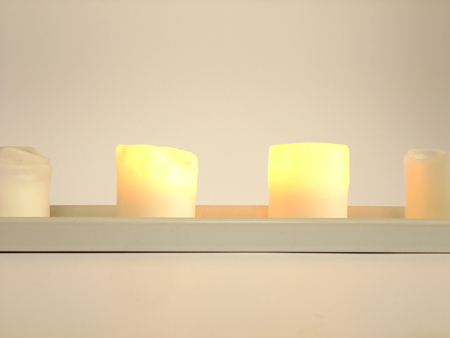 fade away: Two of Four Candles are burning in Candlestick in white Background Stock Photo