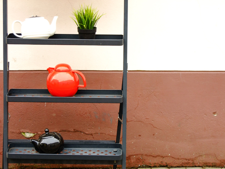 Composition of three Teapots standing of three Shelfs outside old Building Stock Photo