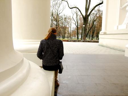 mujer mirando el horizonte: Mujer sentada en columnas Fundación y mirando hacia el parque Foto de archivo