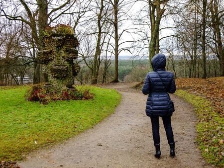 intresting: Woman looking at wooden Sculpture with Flowers in the Park of Lithuania Stock Photo