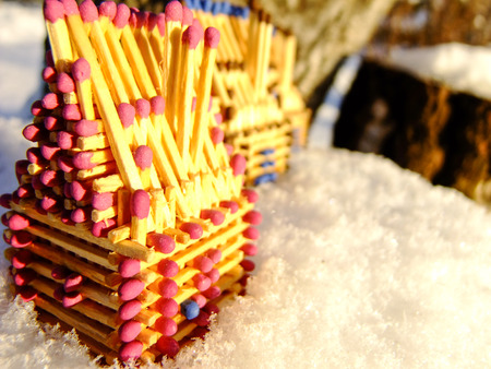 Three Little Houses made of red and blue Matches are standing outdoor on Snow during Sunset