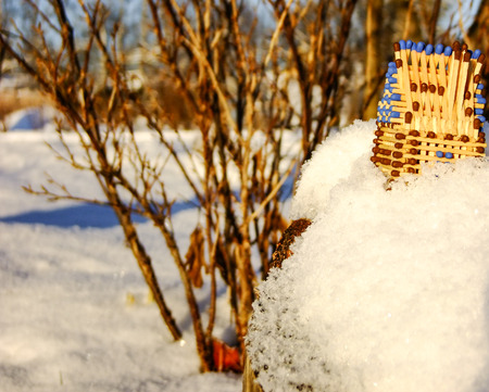 Little House made of blue Matches is standing outdoor on Snowy Cliff during Sunset