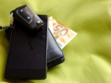 Black Car Keys with small Pendant on top of Smartphone on top of Black Wallet with fifty Euro in greenish Textile Background