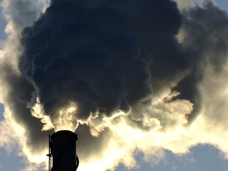 Closeup of high Chimney emits a large amount of Smoke in Vilnius City, Lithuania during the Sunset