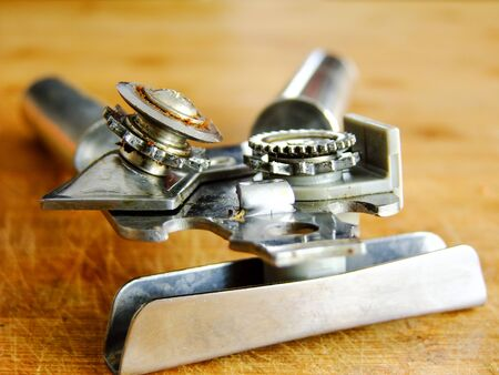 can opener: Closeup of used Can Opener on wooden Cutting Board Stock Photo