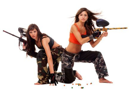 Two young beautiful girls posing like playing paintball