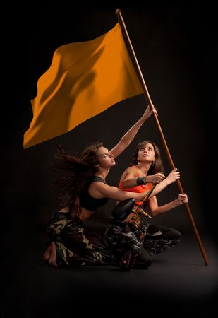 Two young girl rising flag with paintball gun in their hands.  photo