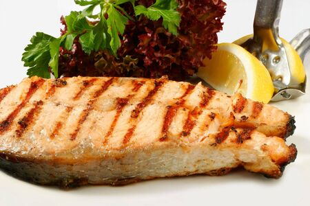 Grilled salmon steak with salad and lemon