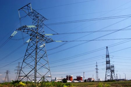 Electrical power lines and nuclear power station under clear blue sky
