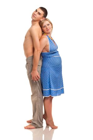 Pregnant woman with her husband standing back to back. Studio shoot on white.