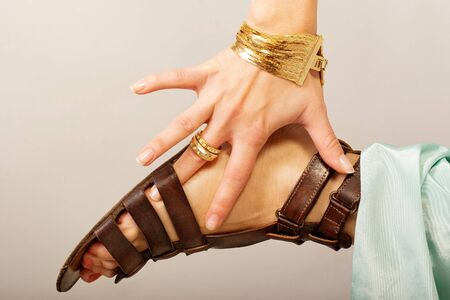 Hand with jewellery holds on feet Stock Photo