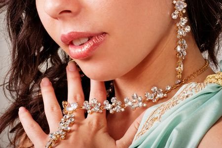 Beautiful young lady shows necklace and earring