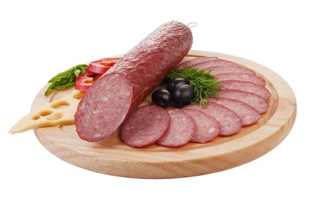 Sliced sausage with vegetables on a wooden plate isolated