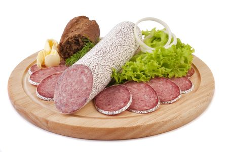 Sliced sausage with rye bread, butter and vegetables on a wooden plate isolated