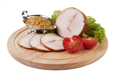 Sliced ham with mustard and vegetables on a wooden plate isolated