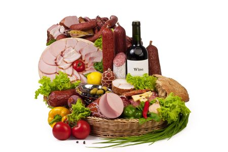 A composition of meat and vegetables with a bottle of wine isolated on white.