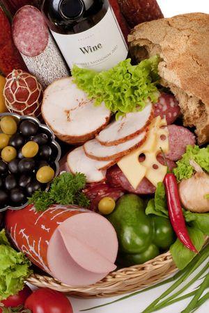 Una composición de carne y verduras con una botella de vino aislado en blanco  Foto de archivo