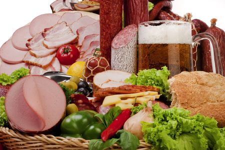 A composition of meat and vegetables with a pot full of beer isolated on white photo