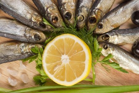 A composition with smoked clupea herring fish (Clupea harengus membras) on wooden plate isolated on white