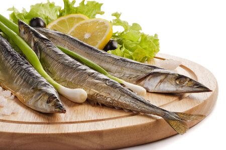 A composition with smoked saira fish (cololabis saira) on wooden plate isolated on white. Closeup