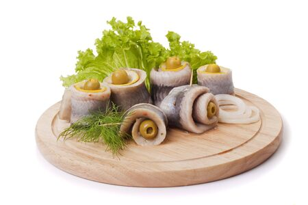 A composition with marinated herring rolls and vegetables on wooden plate isolated on white