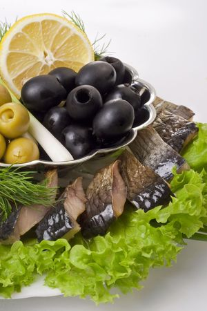 A composition with herring pieces and vegetables isolated on white. Closeup