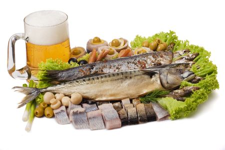 A Goblet of beer and a fish set with herring, mackerel, clupea and vegetables isolated on white