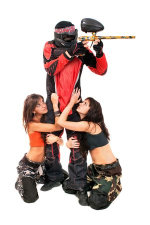 Paintball player with girls on a knees around him