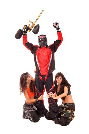 Paintball player with girls on a knees around him photo