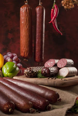 A composition of different sorts of sausages on dark background photo
