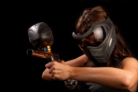 Image of a paintball player in protective helmet aiming the target