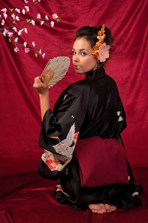 Japanese girl in traditional clothes posing to the camera photo