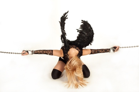 Model in role of black angel trying to break chains