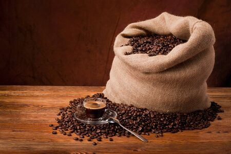 Studio photo of sack with scattered coffee grain, and cup of espresso photo