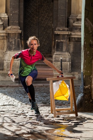 orienteering: Woman punching at control point, taking part in orienteering city race competitions in old european city. File contains clipping path