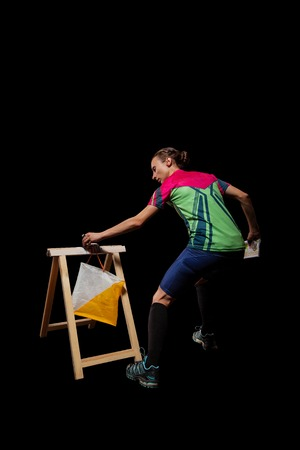 orienteering: Woman punching at control point, taking part in orienteering competitions. Isolated on black. File contains clipping path