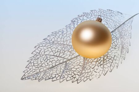 gold silver: New Year background with golden glass toy on silver decorative leaf Stock Photo