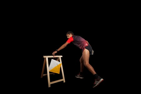 Man punching at control point, taking part in orienteering competitions. Isolated on black. File contains clipping path Stock Photo