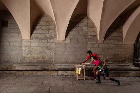 orienteering: Two sportsmens punching at control point, taking part in orienteering city race competitions in old european city
